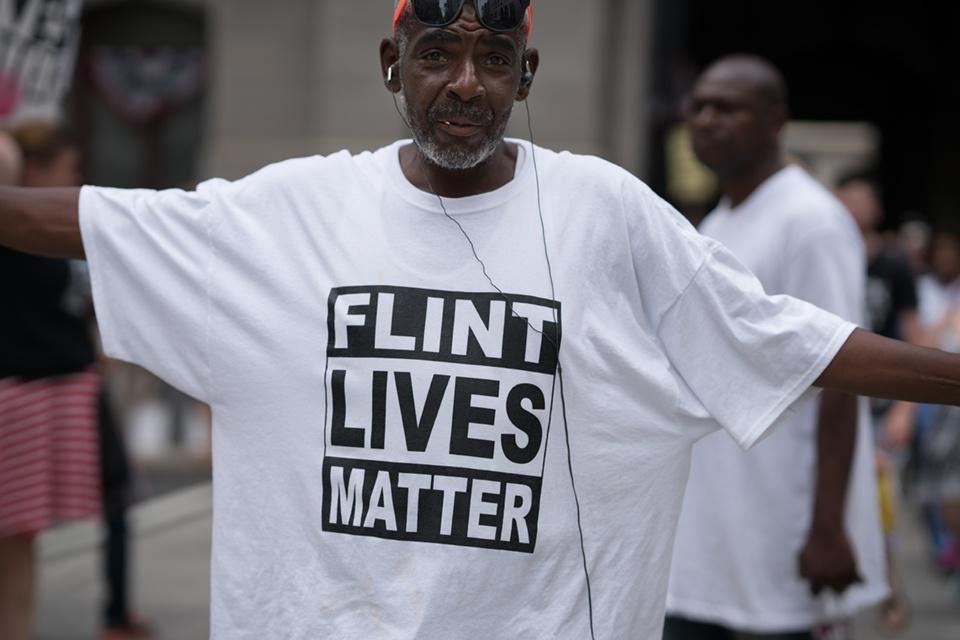 """Man with shirt that reads """"Flint Lives Matter"""""""