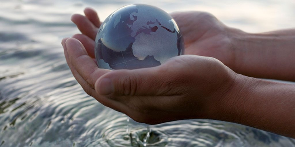 hand with water globe over water