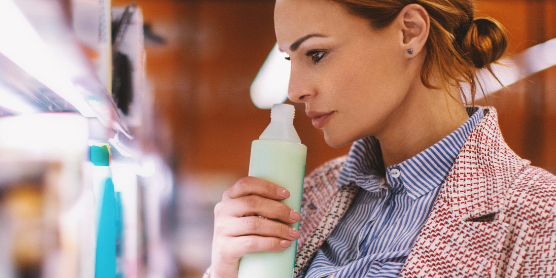 harmful fragrance chemicals - woman smelling bottle opening