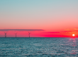 Ocean with Wind Turbines and Sun Setting