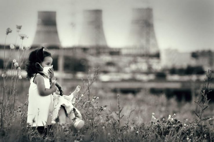 Girl with Mask in Field Nuclear Cooling Towers in Background